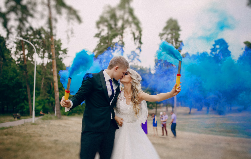 Wedding couple runs blue smoke in the park
